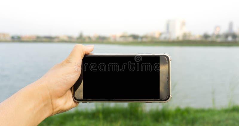 Hand - gehouden smartphone in het park stock afbeelding