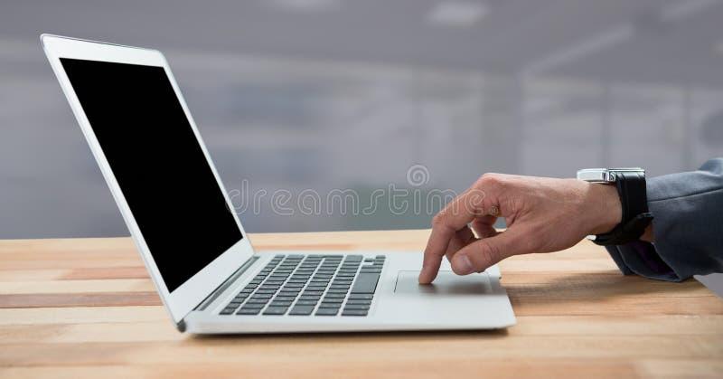 Hand genom att använda bärbara datorn med skrivbordet arkivfoto