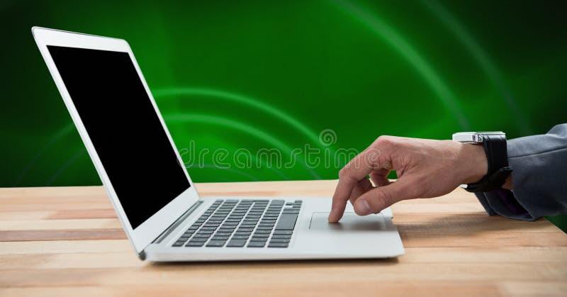 Hand genom att använda bärbara datorn på skrivbordet arkivfoto