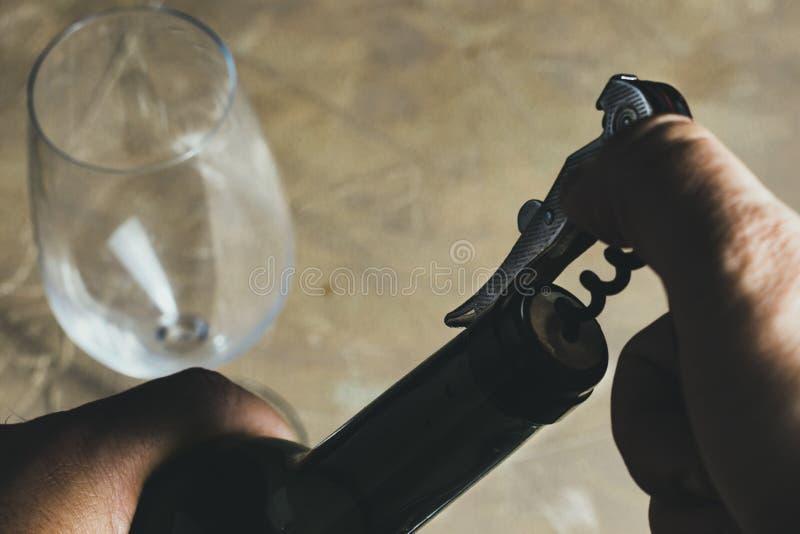 Hand genom att använda korkskruvet för att dra ut kork från en flaska och ett tomt vinexponeringsglas royaltyfri foto