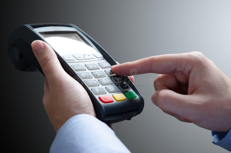 Hand genom att använda kreditkortbetalningmaskinen arkivfoton