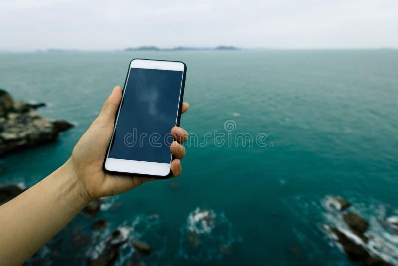 Hand genom att använda smartphonen med havet royaltyfri fotografi
