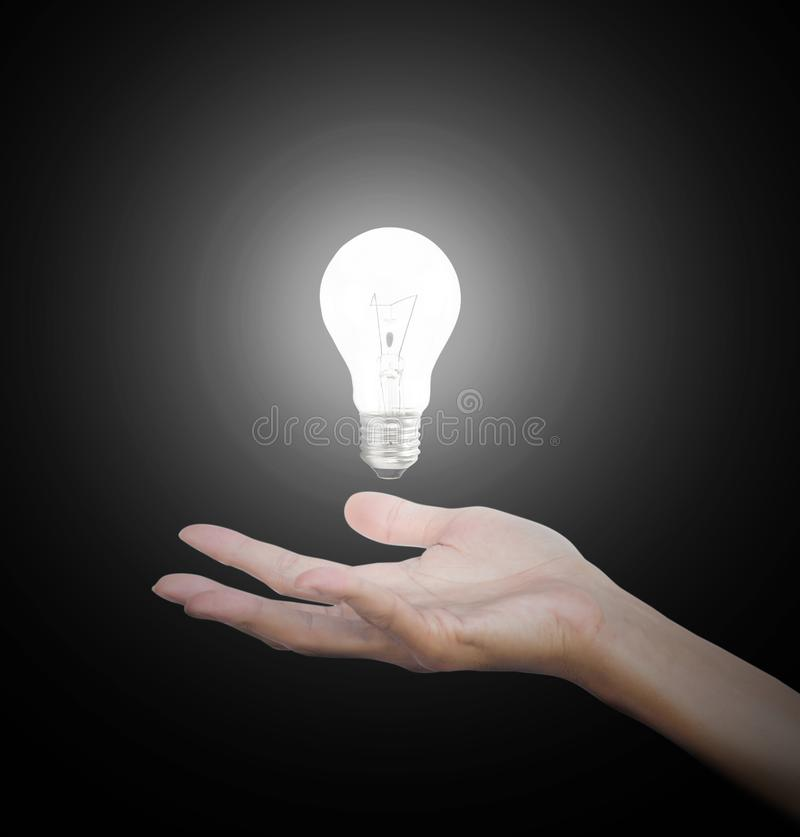 Hand gesture holding floating light bulb with light on dark background. Conceptual thinking new idea. Concept idea. royalty free stock image