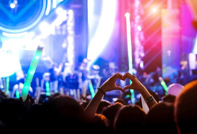 Hand gesture loves finger at concert stage lights. Crowd or audience artist band in the music festival rear view with spotlights glowing effect and people fan stock images