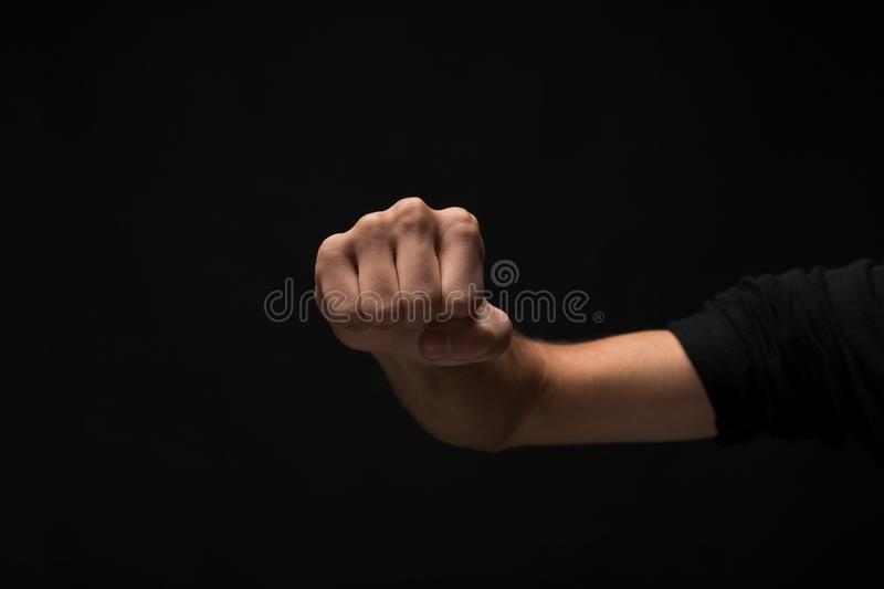 Hand gesture, man clenched fist, ready to punch isolated. Fight hand gesture. Man clenched fist, ready to punch, isolated on black studio background, closeup royalty free stock photos