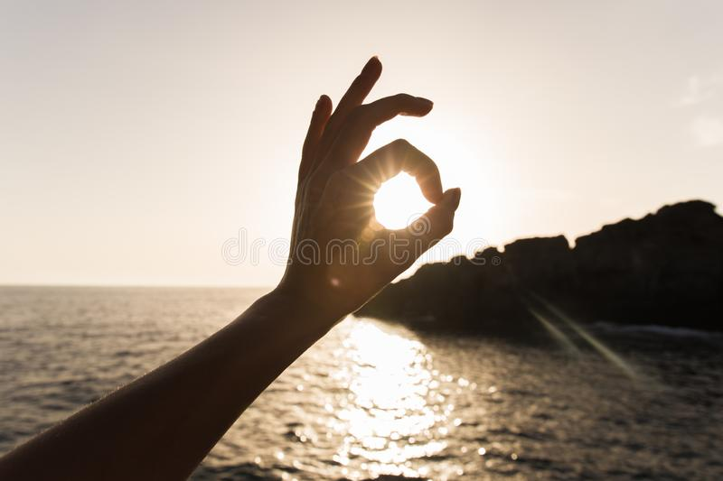 Finger all is well on the sea. mark of approval. hand gestures, sun in hands stock image