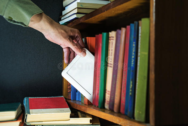 Hand gets ebook from the bookshelf. new technology concept. Mans hand gets ebook among old paper books from the bookshelf. new technology concept royalty free stock photos