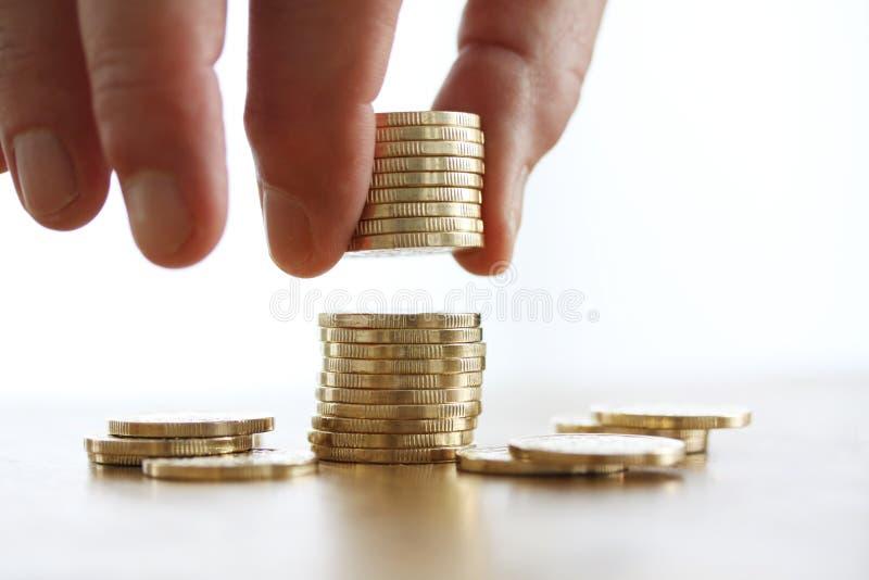 Hand gezet muntstuk aan geldstapel op witte achtergrond Close-up van Hand die een muntstuk zetten aan stapel muntstukken Bedrijfs stock foto's