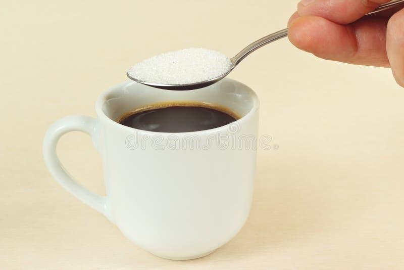Hand gießt Zucker vom Löffel in einer Kaffeetasse lizenzfreie stockfotografie