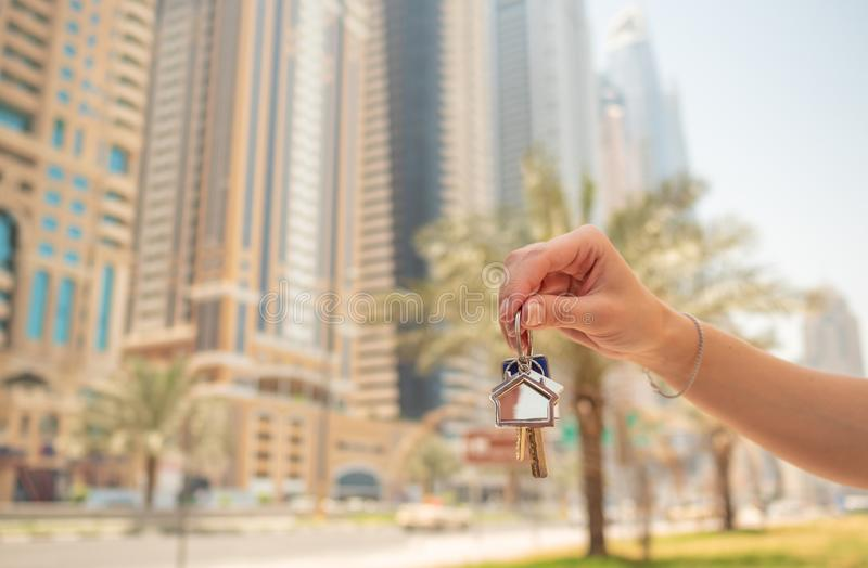 Hand girl holds the keys. The concept of buying an apartment or car in Dubai. Hand close-up. stock photos
