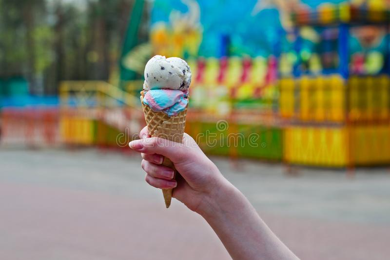 Hand of a girl with an ice cream in an amusement park stock image