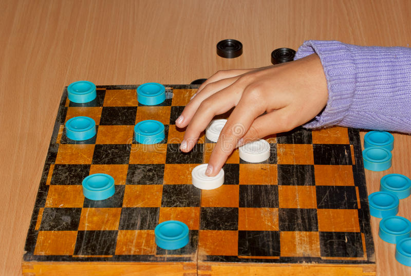 Hand girl moves the checkers on the chessboard. Hand girl moves the checkers on the board royalty free stock photo