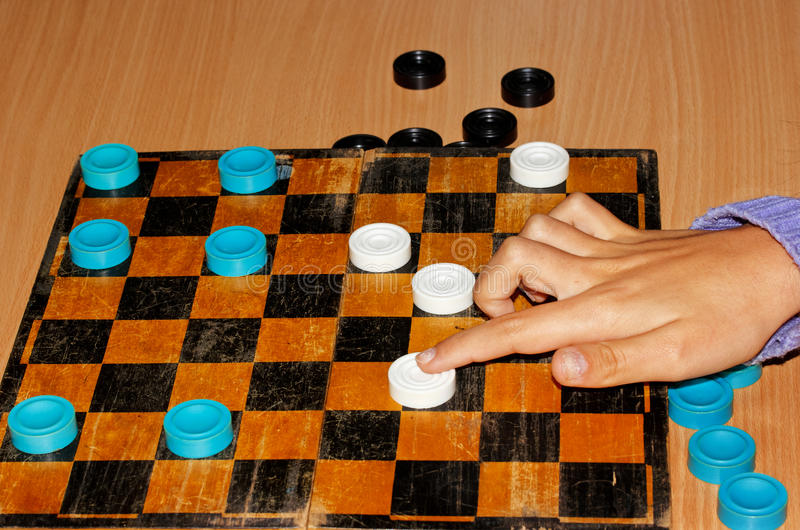Hand girl moves checkers on the chessboard. Hand girl moves checkers on the board royalty free stock photography