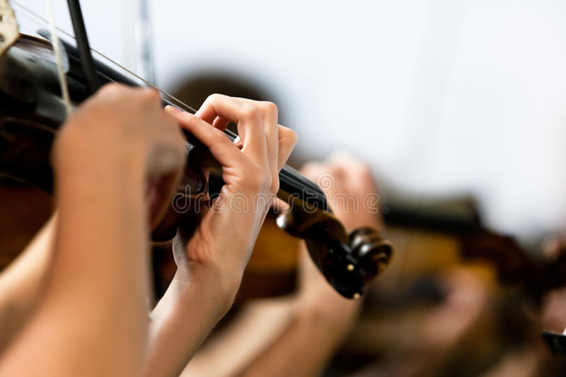 The hand of a girl playing the violin in an orchestra stock image