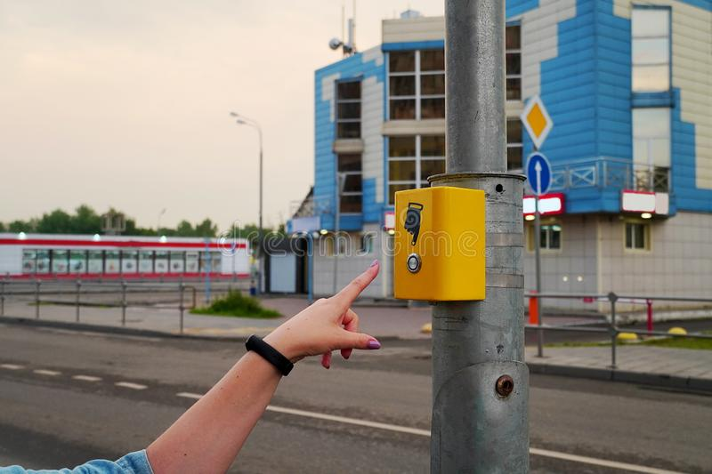 The hand of the girl presses the button of the pedestrian crossing. Yellow button electronic crosswalk. A hand sign indicates a stock photo