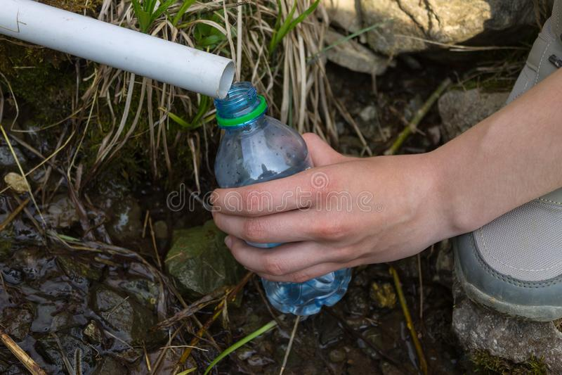 The hand of a girl who collects water in a plastic bottle close-up royalty free stock images