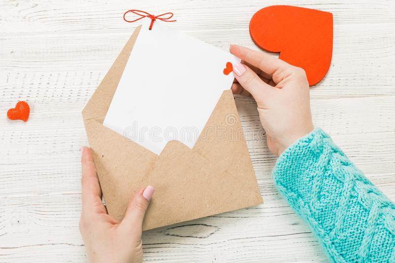 Hand of girl writing love letter on Saint Valentines Day. Handmade postcard with red heart shaped figure. 14 February holiday stock photo
