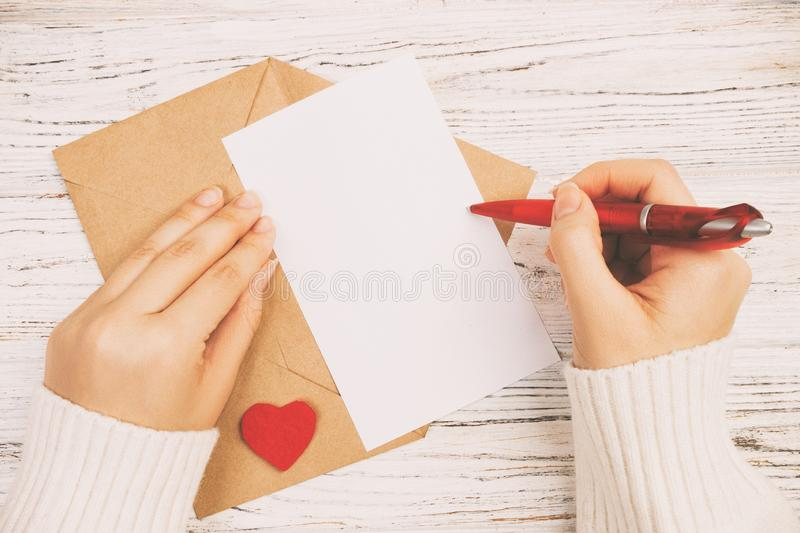 Hand of girl writing love letter on Valentine Day. Handmade postcard toned, vintage. Woman write on postcard for 14 February. Holiday celebration. Flat lay. Top royalty free stock photo