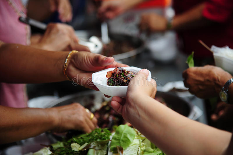 Hand give food to hands of a beggar royalty free stock photo