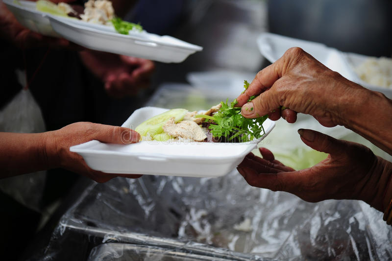Hand give food to hands of a beggar.  royalty free stock images