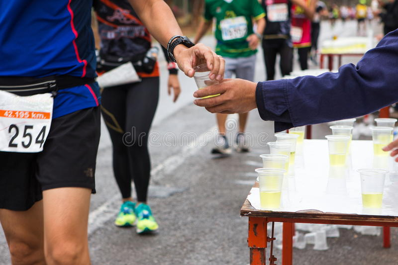 Hand give Minerals water to Unidentified runners royalty free stock photography