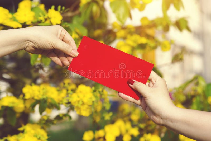 Hand give money in red envelopes - ang pow or red packet to some stock photos