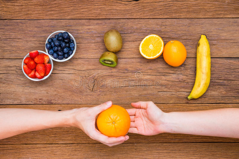 Hand give and take orange. With various fruits on wooden table royalty free stock photography