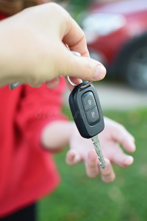 Hand gives car keys to other person stock photo