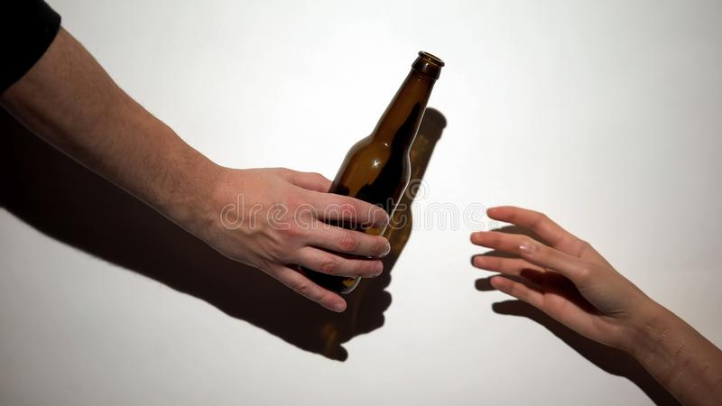 Hand giving beer bottle to alcohol addict with self-inflicted arm, harmful habit royalty free stock photos