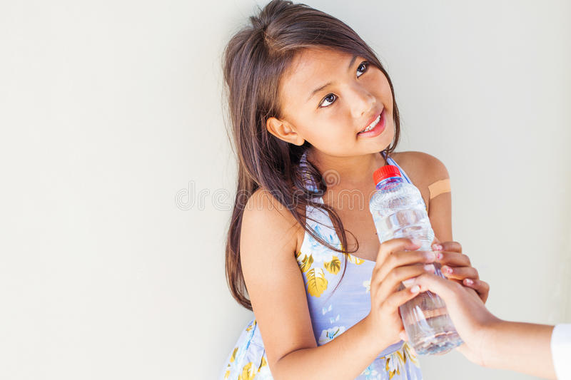 Hand giving a bottle of water to poor child. Helping hand giving a bottle of water to poor child royalty free stock images