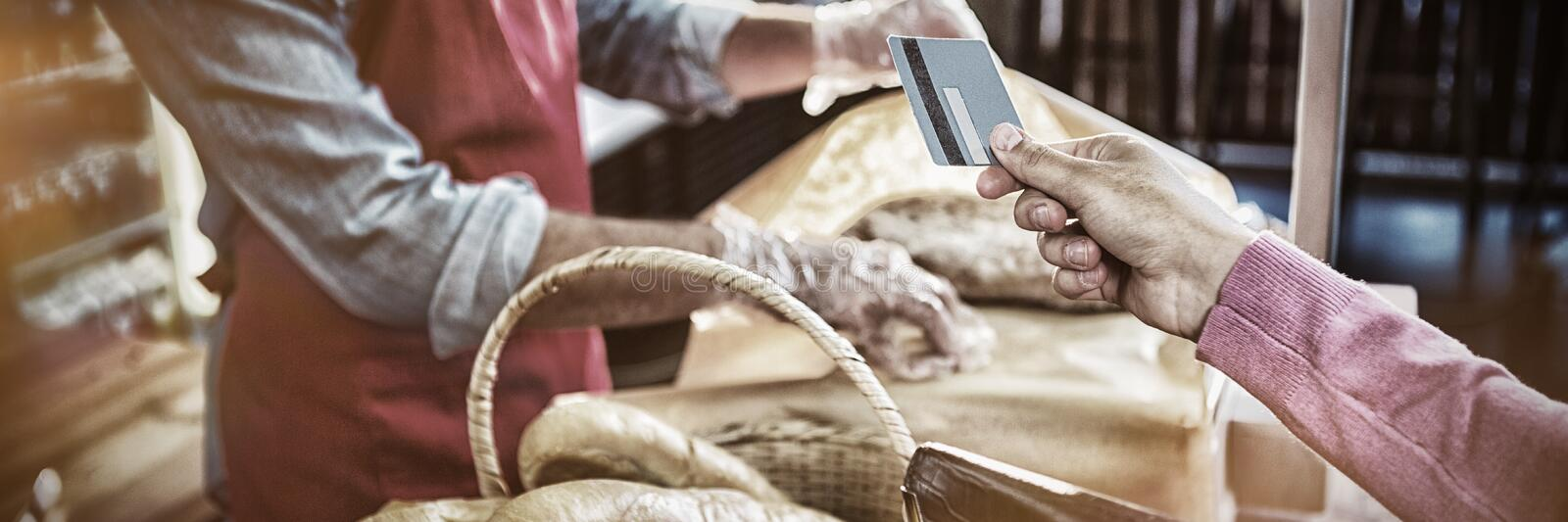 Hand giving credit card at payment counter royalty free stock photo