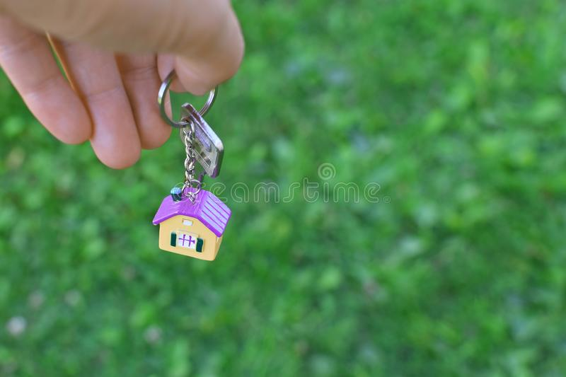 Hand giving key chain with house. Hand giving key chain with colorful house shaped pendant on green blurred grass background with copy space for text. Real stock photography