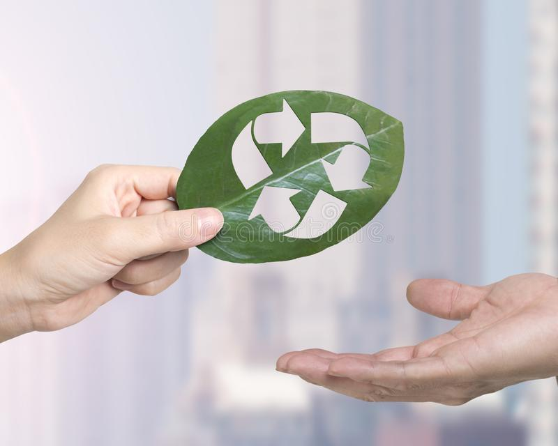 Hand giving leaf with hole of recycling symbol, resource recovery royalty free stock photos