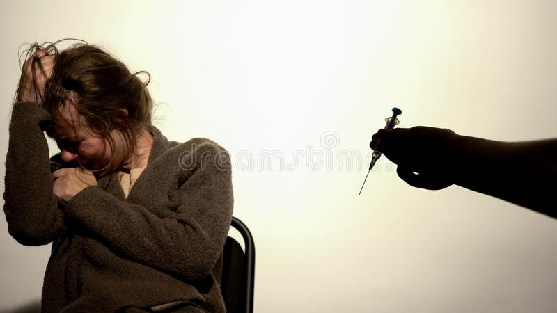 Hand giving syringe to weak-willed female, addiction hopelessness, drugs rehab stock images