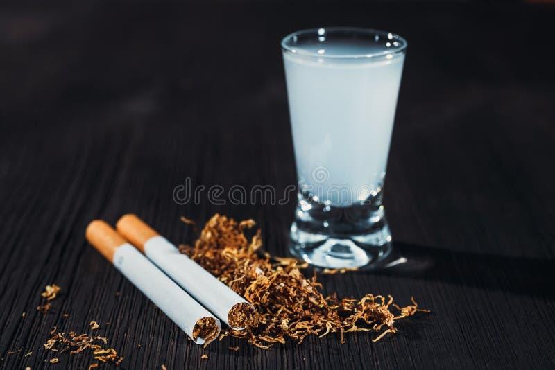 Hand - gjord cigarett och tobak med ett exponeringsglas av vodka royaltyfri fotografi