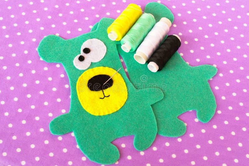 Hand - gjord uppsättning för filtgräsplanbjörn på violett bakgrund med prickar Hur man syr en leksak för nallebjörn moment arkivfoton