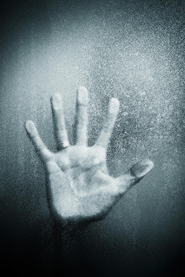 Hand on glass. A handful of leaning on sandblasted glass plate royalty free stock image