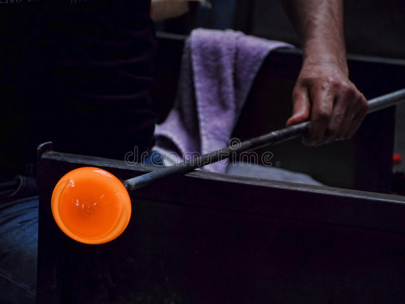 Hand of a glass blower holding a molten `gather`. Free-blowing is a glass blowing technique now mainly used for artistic purposes. It involves blowing puffs of royalty free stock images
