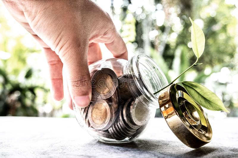 Hand and Glass jar piggy bank with coins. Plan your savings, run a growing business for success and save for retirement royalty free stock images