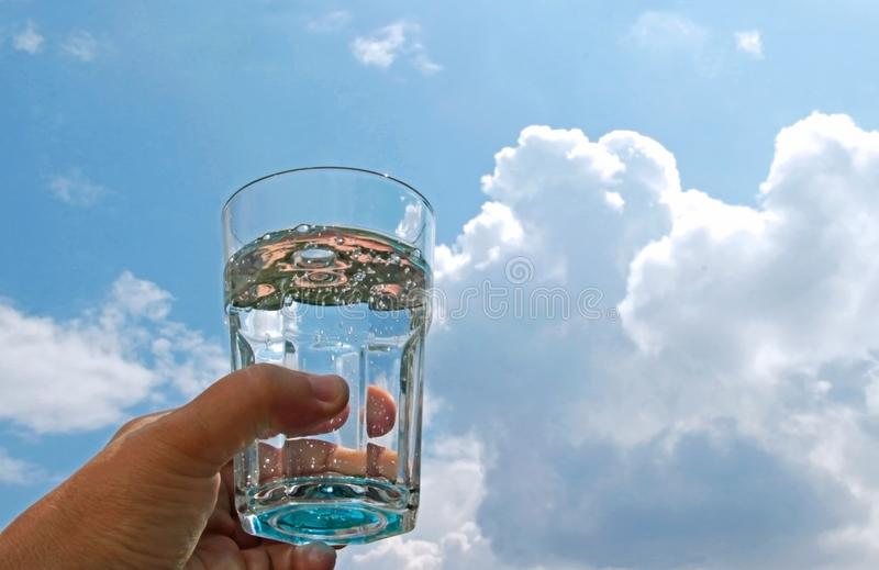 Hand with a glass water in front of blue and white sky stock photos