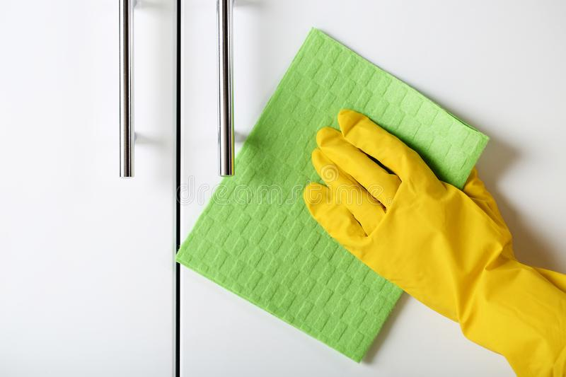 Cleaning kitchen cabinet. Hand in glove cleaning kitchen cabinet royalty free stock photography