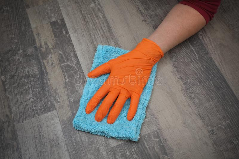 Hand in glove cleaning laminate floor royalty free stock image