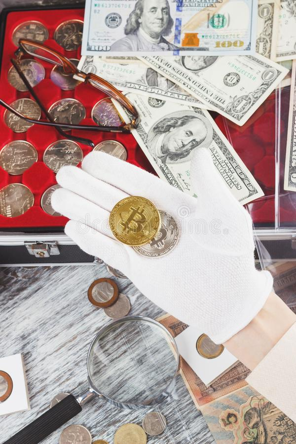 Hand in the glove with a gold and silver coins. Top view stock image