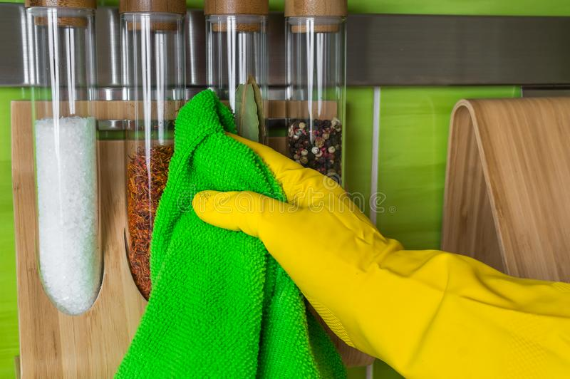 Hand in glove with green rag is wiping spice bottles stock image