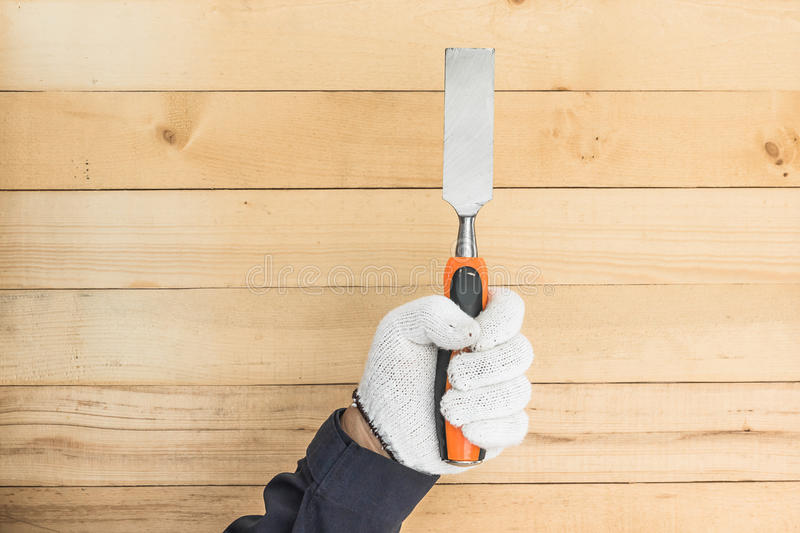 Hand in glove holding chisel. Working hand in glove holding a chisel with wall wood background stock images
