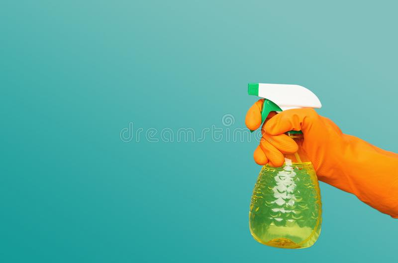 A hand in glove holding spray of cleaning fluid royalty free stock images