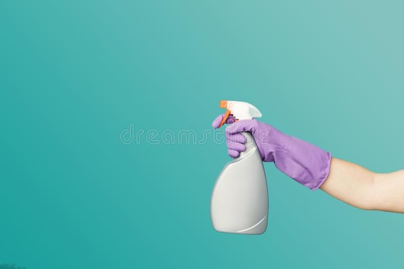 A hand in glove holding spray of cleaning fluid royalty free stock image