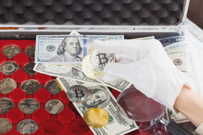 Hand in the glove holds gold and silver coins. Soft focus background stock photos