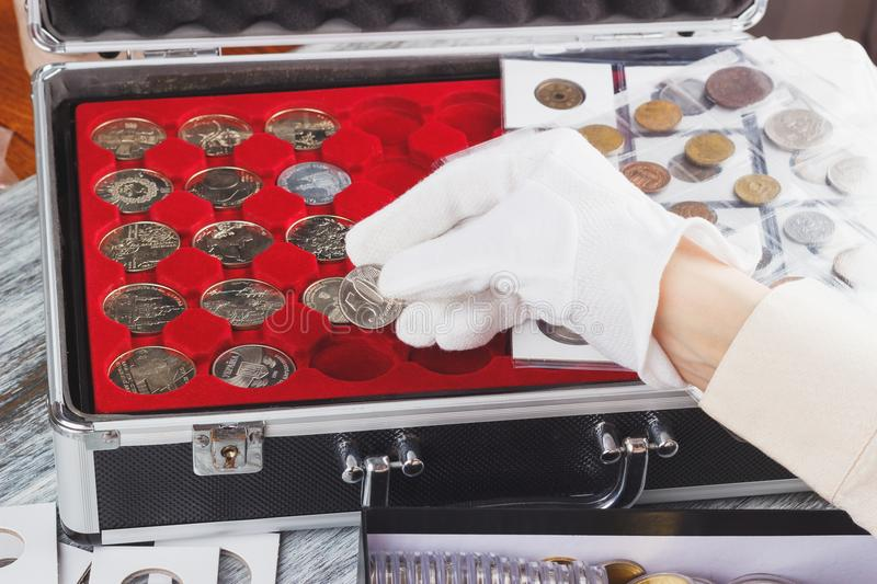 Hand in a glove with a silver coin. Soft focus background stock image