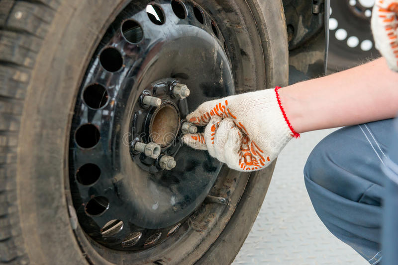 Hand in a glove unscrews the nuts on wheel royalty free stock photo